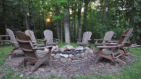 Wooden chairs around a fire